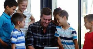 Insegnante e bambini facendo uso della compressa in aula stock footage