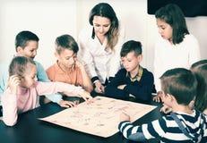 Insegnante e bambini felici che si siedono alla tavola con il gioco da tavolo Immagine Stock