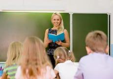Insegnante e scolari in aula alla lezione Fotografia Stock