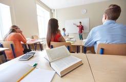 Insegnante e studente al bordo bianco a scuola Immagine Stock Libera da Diritti