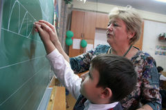 Insegnante e studente alla lavagna immagine stock