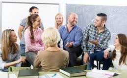 Insegnante e studenti adulti felici Immagine Stock