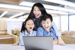 Insegnante e studenti che esaminano computer portatile Fotografia Stock