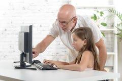 Insegnante e una ragazza della scuola con un computer Fotografia Stock Libera da Diritti