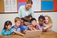 Insegnante ed allievi che esaminano computer portatile Immagine Stock