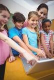 Insegnante ed allievi che esaminano computer portatile Fotografia Stock Libera da Diritti
