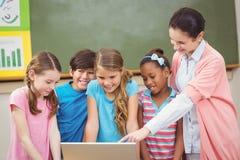 Insegnante ed allievi che esaminano computer portatile Fotografie Stock Libere da Diritti