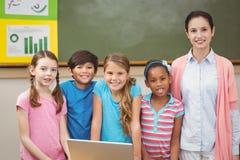 Insegnante ed allievi che esaminano computer portatile Fotografia Stock