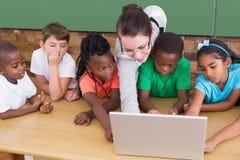 Insegnante ed allievi che lavorano al computer portatile Fotografie Stock Libere da Diritti