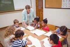 Insegnante ed allievi che lavorano insieme allo scrittorio Immagini Stock