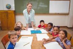 Insegnante ed allievi che lavorano insieme allo scrittorio Fotografie Stock