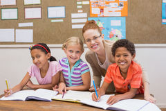 Insegnante ed allievi che lavorano insieme allo scrittorio Fotografia Stock
