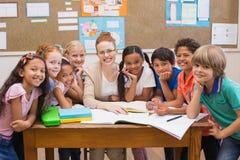 Insegnante ed allievi che lavorano insieme allo scrittorio Immagine Stock Libera da Diritti