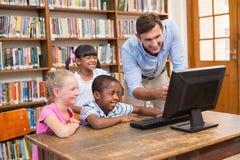 Insegnante ed allievi che per mezzo del computer alla biblioteca Fotografia Stock