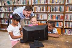Insegnante ed allievi che per mezzo del computer alla biblioteca Fotografia Stock Libera da Diritti