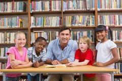 Insegnante ed allievi che sorridono alla macchina fotografica alla biblioteca Immagini Stock