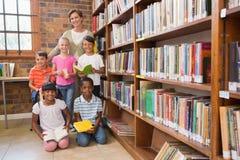 Insegnante ed allievi che sorridono alla macchina fotografica alla biblioteca Immagine Stock