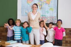 Insegnante ed allievi che sorridono alla macchina fotografica in aula Fotografie Stock Libere da Diritti