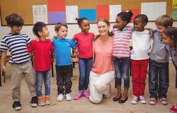 Insegnante ed allievi che sorridono alla macchina fotografica in aula Fotografia Stock