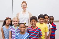 Insegnante ed allievi che sorridono alla macchina fotografica in aula Fotografia Stock Libera da Diritti