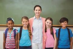 Insegnante ed allievi che sorridono alla macchina fotografica in aula Immagini Stock