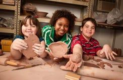 Insegnante ed allievi nello studio dell'argilla Immagine Stock