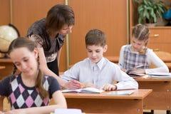 Insegnante ed allievo in aula che imparano insieme Il bambino guarda insieme all'insegnante in libro Ciò dice a bambino il compit Fotografia Stock Libera da Diritti
