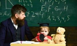 Insegnante ed allievo che si siedono nell'aula L'uomo adulto in vestito astuto sta guardando al lato mentre il bambino sta giocan Fotografie Stock Libere da Diritti