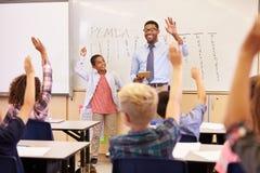 Insegnante ed allievo con le mani sollevate alla parte anteriore della classe di scuola Fotografie Stock Libere da Diritti