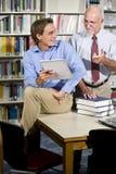 Insegnante ed allievo dell'istituto universitario che comunicano nella libreria Fotografia Stock