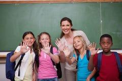Insegnante ed i suoi allievi che ondeggiano alla macchina fotografica Fotografie Stock