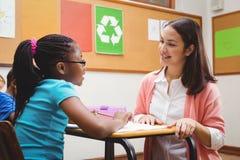 Insegnante felice che aiuta i suoi studenti Immagini Stock