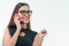 Insegnante femminile attraente, donna di affari, vetri d'uso con il telefono, sorridente sul fondo bianco, spazio della copia fotografia stock libera da diritti