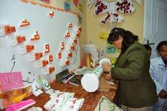 Insegnante femminile che controlla il gioco di puzzle, gioco di parole sulla lavagna Fotografia Stock