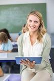 Insegnante femminile che utilizza compressa digitale nella classe Immagine Stock