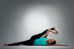 Insegnante femminile di forma fisica che si trova sul pavimento che fa yoga Immagine Stock