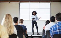 Insegnante femminile With Digital Tablet che dà presentazione alla classe di High School in Front Of Screen fotografia stock libera da diritti