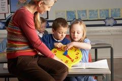Insegnante femminile nei bambini d'istruzione del banco primario Fotografia Stock
