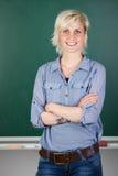 Insegnante femminile sicuro In Front Of Chalkboard Fotografia Stock Libera da Diritti