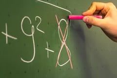 Insegnante femminile Writing della mano sul professor verde Univer della lavagna Immagine Stock Libera da Diritti