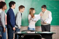 Insegnante Gesturing Thumbsdown While che esamina Fotografia Stock Libera da Diritti