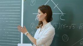 Insegnante grazioso che parla con allievi in aula Immagini Stock Libere da Diritti