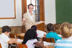 Insegnante grazioso che parla con giovani allievi in aula Immagine Stock Libera da Diritti