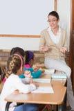Insegnante grazioso che parla con giovani allievi in aula Fotografia Stock Libera da Diritti
