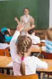 Insegnante grazioso che parla con giovani allievi in aula Immagini Stock