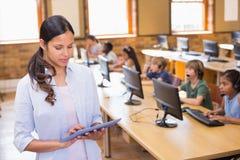 Insegnante grazioso che utilizza il computer della compressa nella classe del computer immagine stock