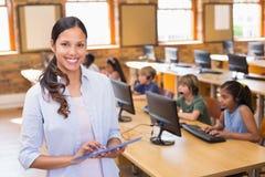 Insegnante grazioso che utilizza il computer della compressa nella classe del computer fotografia stock libera da diritti