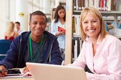 Insegnante Helping College Student con gli studi in biblioteca fotografie stock