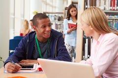 Insegnante Helping College Student con gli studi in biblioteca fotografia stock