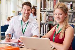 Insegnante Helping College Student con gli studi in biblioteca immagini stock